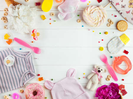Baby shower party background: baby clothes, accessories and candies on the white wooden background with copy space top view, flat lay Фото со стока