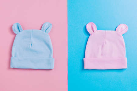 Baby accessories background: funny baby's caps with ears over pink and blue background with copy space top view, flat lay