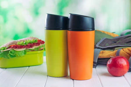 Color thermal mugs near lunch box and backpack on the white wooden table selective focus