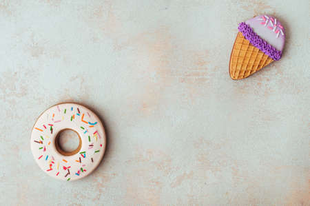 Funny donut and ice cream cone shape cookies on beige background with blank space for text top view, flat lay