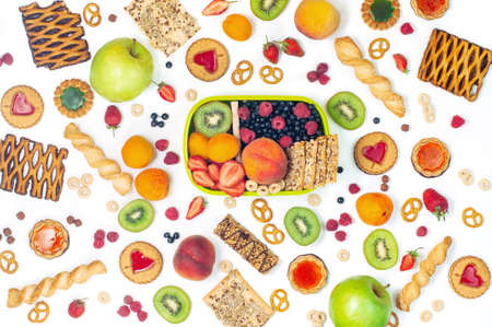 Summertime healthy food concept: Lunch box and variety of fruits, berries, cookies and crunches around it on white background top view, flat lay