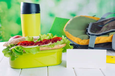 Lunch box with sandwich near card with blank space for text on white wooden background selective focus