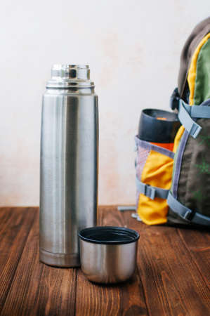 Open thermal bottle with boiling water on wooden background near backpack selective focus