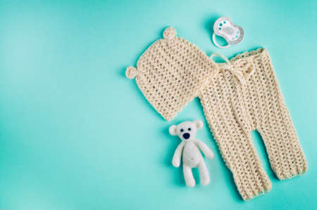 Baby accessories background: small hat and pants for newborn baby, dummy and bear toy on blue background with copy space top view, flat lay Фото со стока