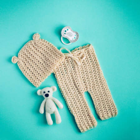 Baby accessories square background: small hat and pants for newborn baby, dummy and bear toy over light green background with copy space top view, flat lay