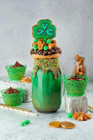 St. Patrick's Day party table: Green freak shake topping with clover and rainbow cookies, donut, caramel popcorn and chocolate cupcakes on gray background selective focus. Stockfoto