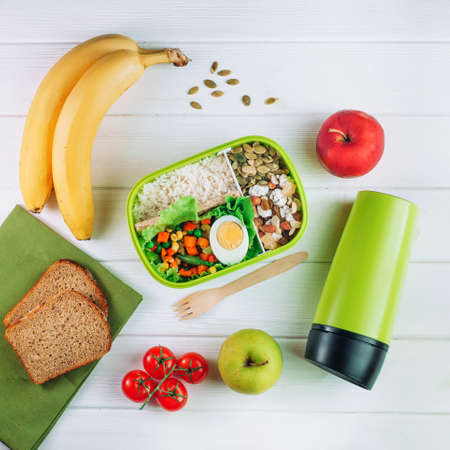 Healthy food concept: Lunch box filled with rice, mixed vegetables, boiled egg and nuts on white wooden background top view, flat lay