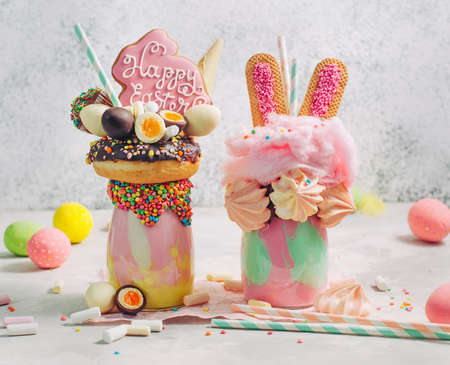 Two Easter freak shakes decorated with rabbit gingerbread and rabbit ears cookies topping with donut, chocolate eggs and cotton candy on party table selective focus.