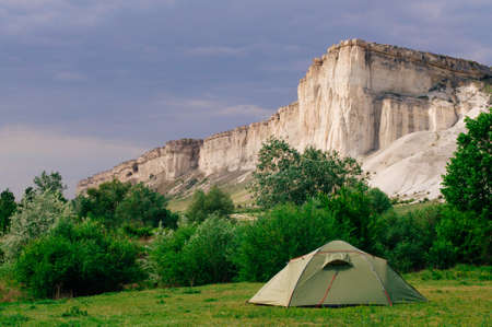 Tourist tent on the summer meadow in front of limestone mountain rocky cliff, selective focus