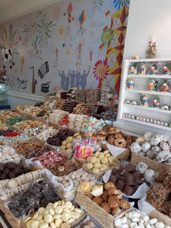 Display window of a bakery and pastry shop with assortment of different kinds of freshly baked local sweets: cookies, biscuits, candies. Cuenca / Ecuador.