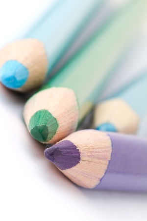 Four colorful crayons on white background with a shallow depth of field for effect. photo