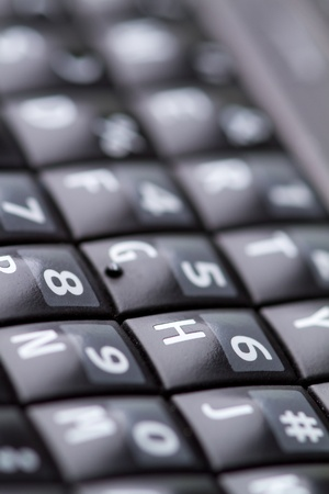 communicative: qwerty keypad from a smartphone shot with a narrow depth of field.