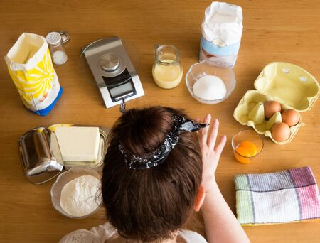 Woman surrounded by baking ingredients on a table in top view