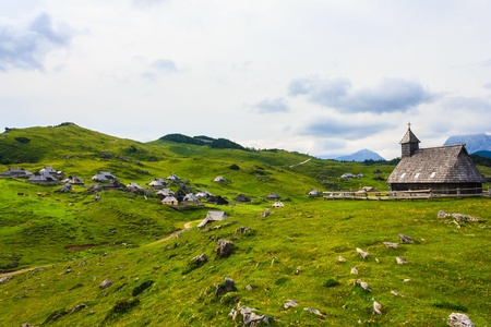 view: Beautiful landscape of spring field on mountain with view of cottages and wooden church on cloudy day