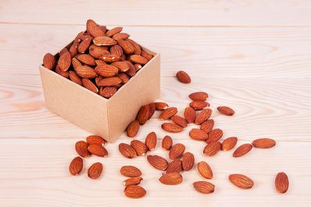 Almonds in wooden bolw on wooden floor