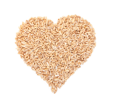 kasha: Oat grains laid out in the shape of heart isolated on white. Top view.