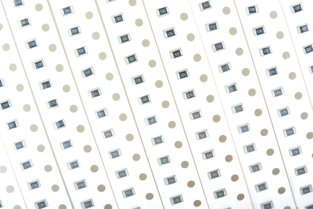 resistors: Perforated tapes with SMD chip resistors for soldering by robot on PCB board close up top view