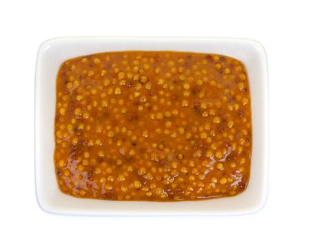 ramekin: Mustard in a ramekin, isolated against white background. Close-up, top view.