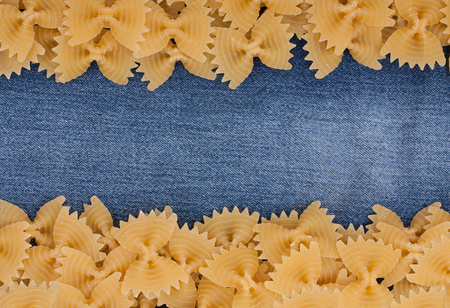 butterfly bow: Background of Italian pasta, pasta made from durum wheat in the shape of a butterfly or bow knot on a jeans fabric with empty space for your text.