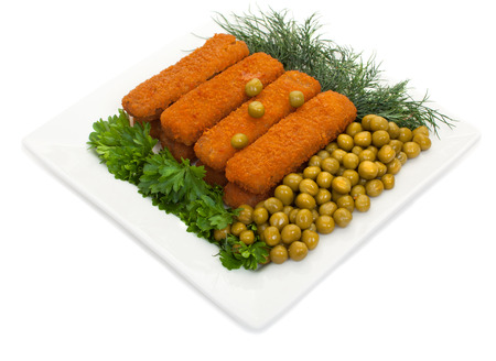 Fish sticks with parsley, dill and canned green peas on a white plate. Isolated on white background.