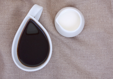 creamer: Cup of coffee on linen tablecloths with creamer and empty place for your text. Close-up, a top plan view.