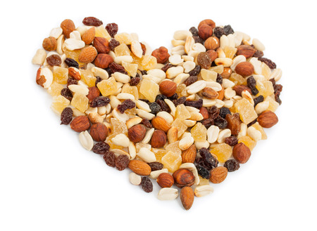 Mixture of nuts and candied fruits isolated on a white background. Fruit Mix in the shape of a heart close-up.