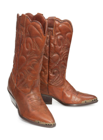 heelpiece: Womens fashion boots. Ladies vintage leather cowboy shoes. Isolated on a white background, close-up.