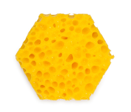 Unusual, hexagonal sponge for washing and cleaning of kitchen ware. Isolated on a white background, close-up, top view. Stock Photo