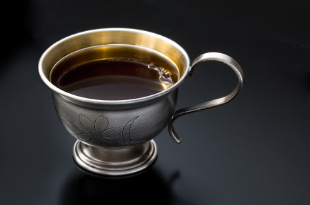 Vintage silverware, very old rich decorated metal cup of coffee on a black surface, close up. Stock Photo