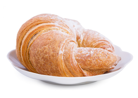 buttered: Fresh croissant on a saucer isolated on a white background, close up.