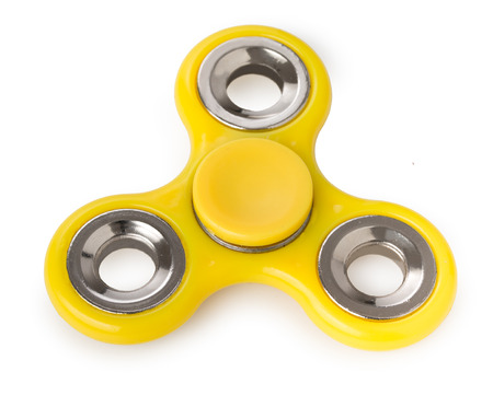 roller: Yellow spinner toy, for stress relieving isolated on a white background. Stock Photo