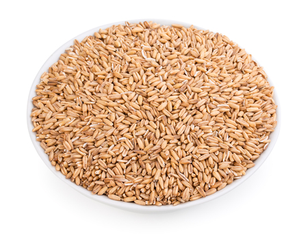 Whole oatmeal groats, oat grains, seeds, kernels, healthly diet food in a ceramic white bowl. Isolated on white background, close-up, top view.