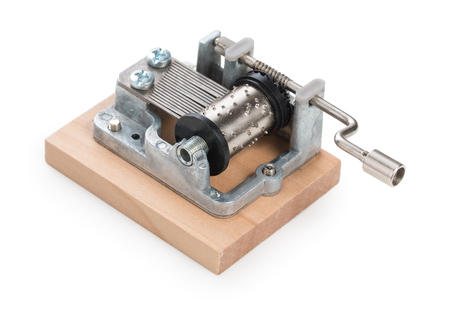 Vintage mechanical music box on a little wooden plank, isolated on white background. Stock Photo