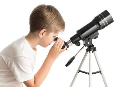 Un giovane ragazzo guarda attraverso un telescopio isolato su uno sfondo bianco.