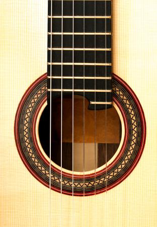 Resonanzboden mit rundem Stimmloch und Saiten der akustischen klassischen Gitarre aus nächster Nähe. Standard-Bild