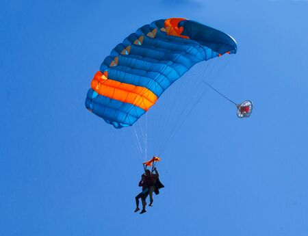 Pair of skydivers on a blue sky background. Tandem parachuting. Canopy in the sky.
