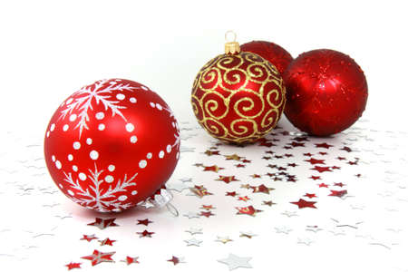 Three red glass christmas baubles on white background with silver stars