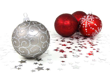 Four red and silver christmas baubles with silver stars on white background