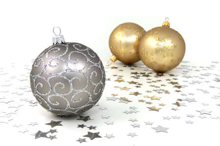 Three silver and golden christmas baubles with silver stars on white background
