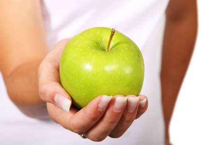 young woman holding fresh green apple in her palm Stock Photo