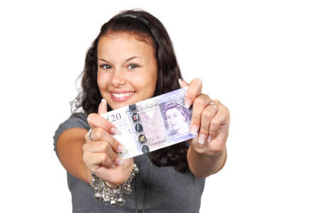 pound sterling: Young woman showing twenty pounds bill isolated on white background