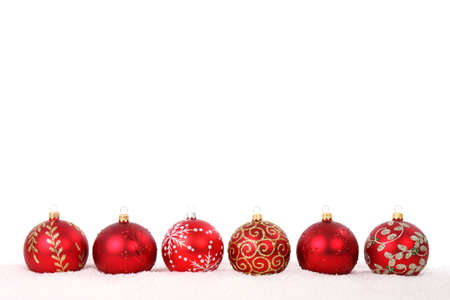 Red christmas baubles in line in snow isolated on white background