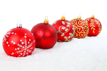 Red Christmas baubles in snow isolated on white background