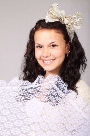 Young woman smiling with white summer umbrella and bow in her hair