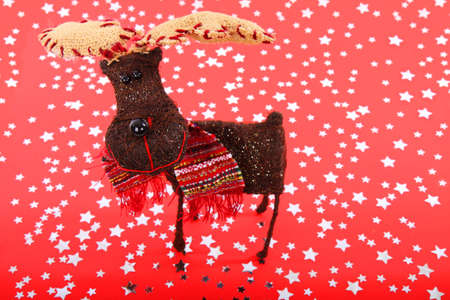 Smiling reindeer on red background with silver stars