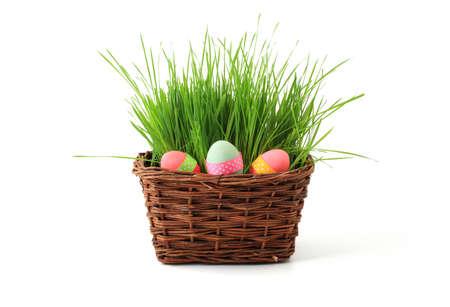 Concept de P�ques - panier avec des herbes fra�ches et oeufs color�s isol�es sur fond blanc
