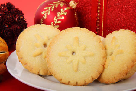 christmas mince pies on plate with red decoration
