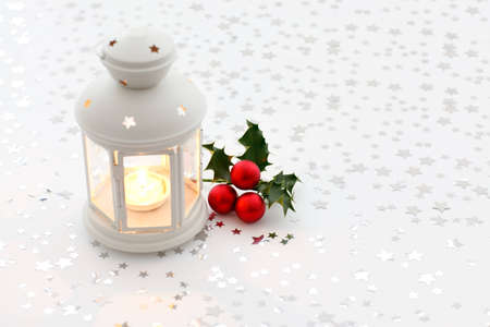 lantern and holly on starry background Stock Photo