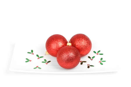 Three red baubles with holly decoration on a plate isolated on white background
