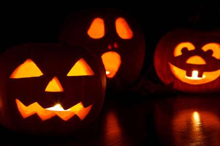 three jack-o-lantern pumpkins glowing in the dark